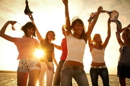 personas: grupo de j�venes felices bailando en la playa en la puesta de sol hermosa del verano Foto de archivo