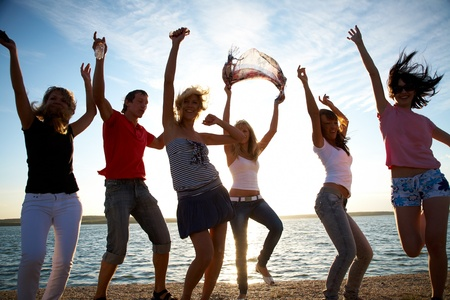 group of happy young people dancing at the beach on  beautiful summer sunset Stock Photo - 12970711