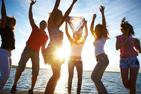 persone che ballano: gruppo di giovani che ballano felici in spiaggia al tramonto bella estate