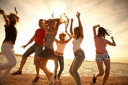 feste feiern: Gruppe gl�ckliche junge Menschen tanzen am Strand am sch�nen Sommer Sonnenuntergang