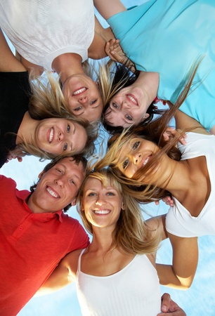 jugendliche gruppe: Gruppe von jungen Leuten fr�hlich und eng umarmt Skyline