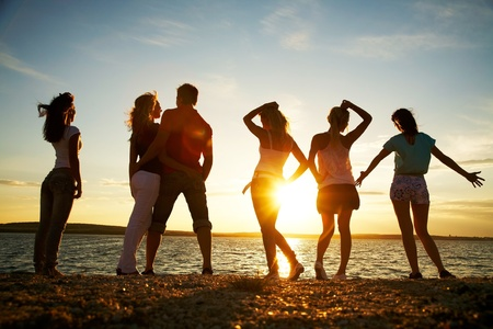 happiness people silhouette on the sunset: group of happy young people dancing at the beach on  beautiful summer sunset