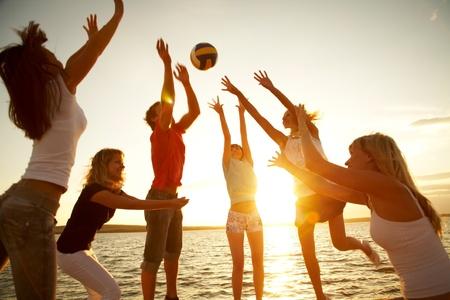 pelota de voleibol: grupo de personas jóvenes jugando voleibol en la playa Foto de archivo