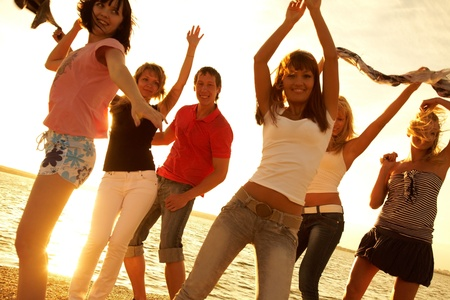 company party: group of happy young people dancing at the beach on  beautiful summer sunset