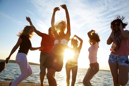 people dancing: gruppo di giovani che ballano felici in spiaggia al tramonto bella estate