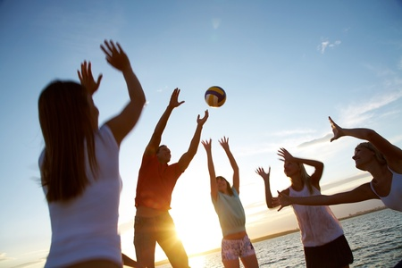 group of young people playing volleyball on the beach photo
