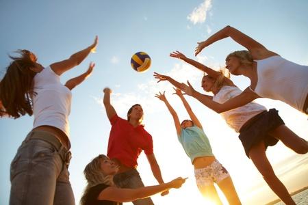 grupo de jóvenes jugando voleibol en la playa