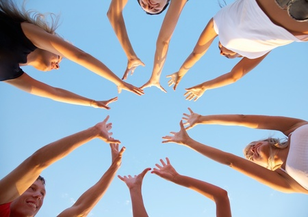 hands of young people stretching to the center