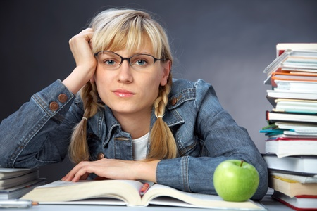 portrait of tiredness girl student reading  book in classroom photo