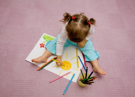 baby drawing: The small beautiful girl draws pencils on a paper the sun sitting on a floor Stock Photo