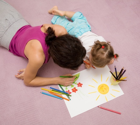 children painting: Beautiful mother draws with a small daughter lying on a floor Stock Photo