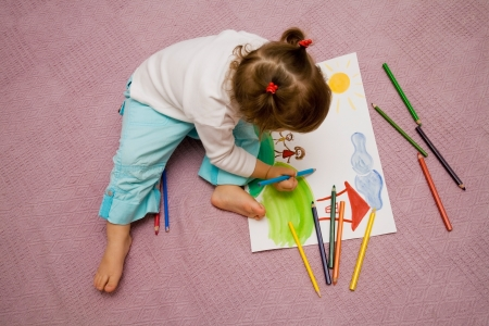 draws: The small beautiful girl draws pencils on a paper the sun sitting on a floor Stock Photo