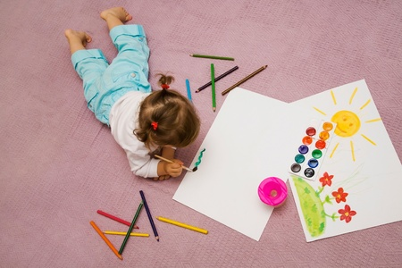 The small beautiful girl paints on a paper lying on a floor photo