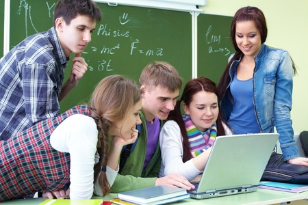 group of young students studying in the classroom with a laptop photo