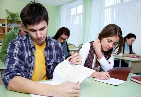 takes: group of students takes the exercise  in classroom