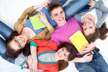 grupo de amigos adolescentes mirar hacia arriba a la cámara con sonrisas brillantes Foto de archivo