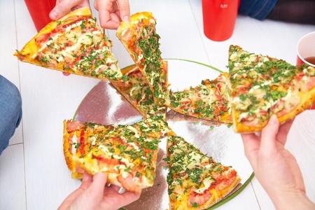 slices of pizza is lifted from human hands photo