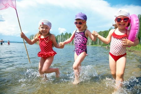 kids swimming: Three little funny  cute girls running on coast together  Stock Photo
