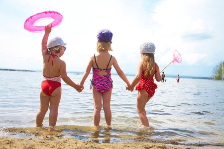 swimming at the beach: Three little cute girls go swimming in the lake