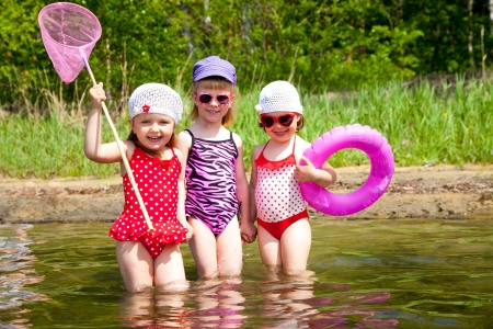 little girl beach: Three little cute girls go in water  together Stock Photo