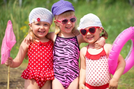 swimsuit: Three little cute girls having good summertime  Stock Photo