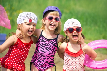 child swimsuit: Three little cute girls go swimming in the lake