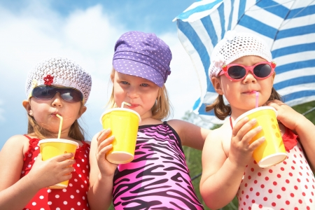 Three little cute girls drinking on the beach