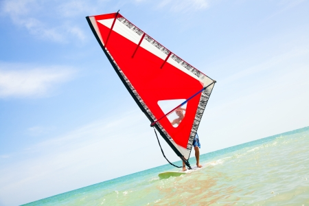 young man riding  red windsurfing sail on the sea photo