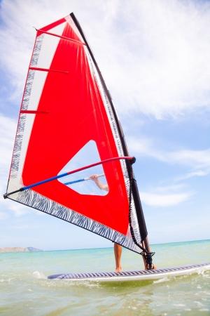 windsurf: el hombre joven que monta la vela de windsurf en el mar rojo Foto de archivo