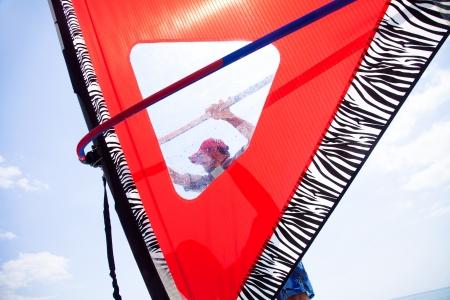 windsurf: chico guapo aferrarse a la vela de windsurf a caballo en el mar Foto de archivo