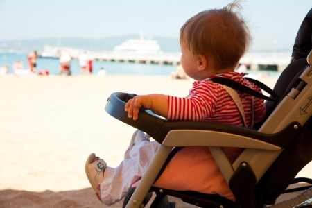 stroller: baby in the stroller watching the sea at the beach resort