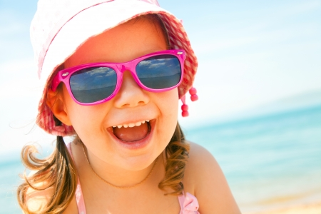 sunglasses beach: happy little girl at the seaside in the summer