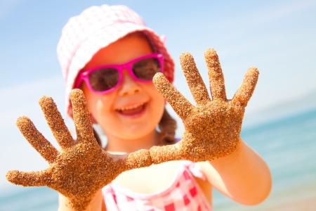 traje de bano: ni�a feliz en la playa en el verano