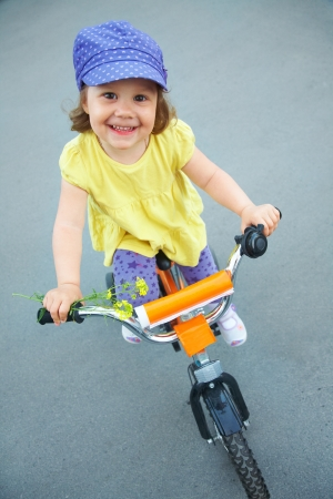 A little cute girl rides a bicycle down the street photo