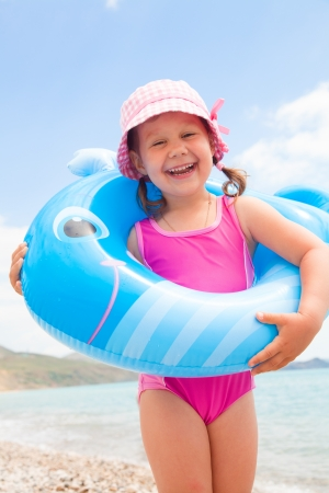 child on the beach: little girlt wants to swim with inflatable whale on the sea Stock Photo