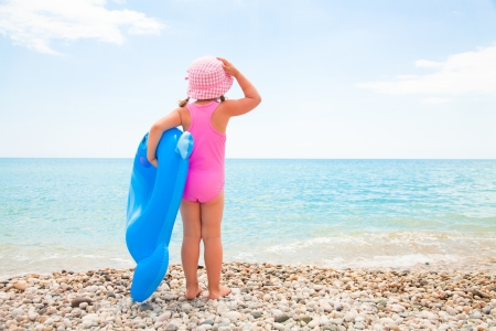 little girl in swimsuit looks at the sea and holds an inflatable toy photo
