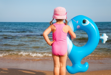 whale: little girl in swimsuit looks at the sea and holds an inflatable toy