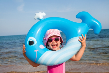 klein meisje op strand: klein meisje in badpak te spelen met een opblaasbare walvis op het strand plaats