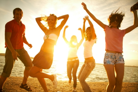 summer festival: happy young teens dancing at the beach on  beautiful summer sunset
