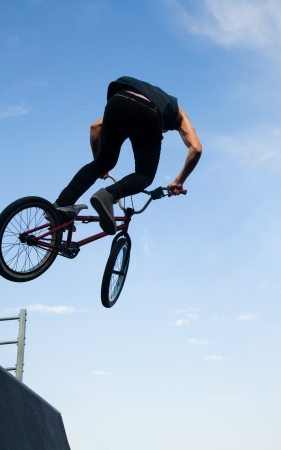 young  boy is jumping with his BMX Bike at the skate park  photo