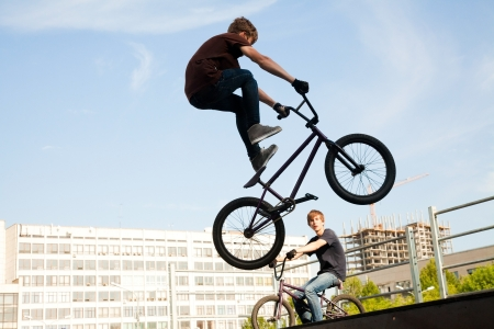 city bike: young  boy is jumping with his BMX Bike at the skate park