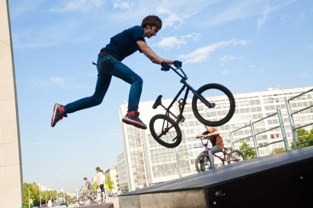 bmx bike: young  boy is jumping with his BMX Bike at the skate park