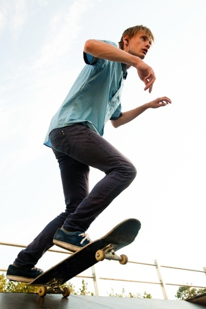 Teenager - skateboarder standing on the start. View from below. photo