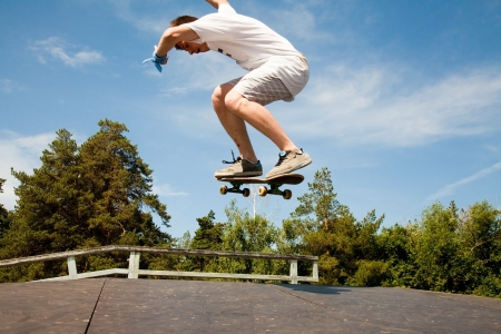 boy skater: Skater jumps high in air on background blue sky  Stock Photo