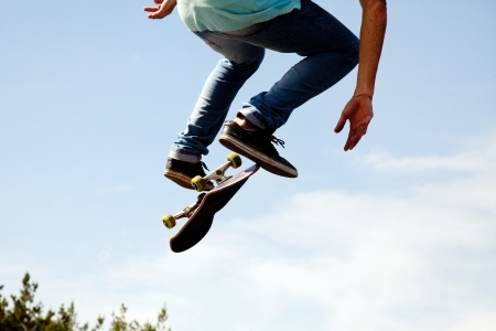 Skater jumps high in air on background blue sky  photo
