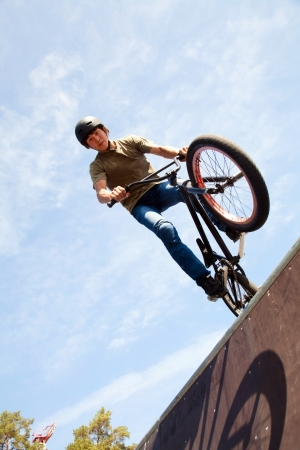 on ramp: Young man  riding on a BMX bicycle on a ramp over blue sky background  Stock Photo
