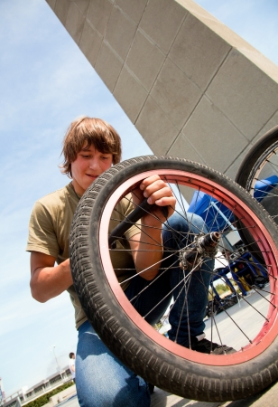 Young guy pumps BMX-  bicycle tire photo