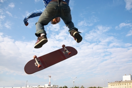 Skater jumps high in air on background blue sky  Imagens