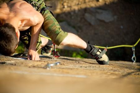 overcoming: escalador joven sube a la colina con un aseguramiento