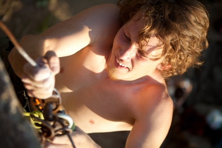 belay: young rock climber with red hair climbs the cliff with a belay